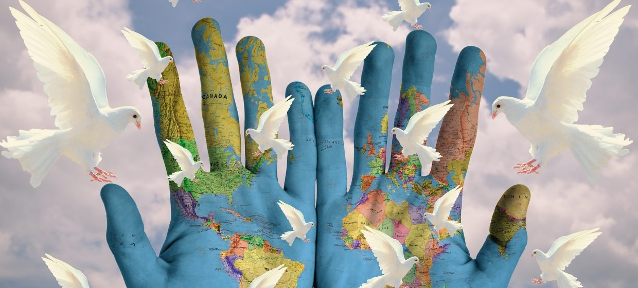 A world map painted on hands with doves
